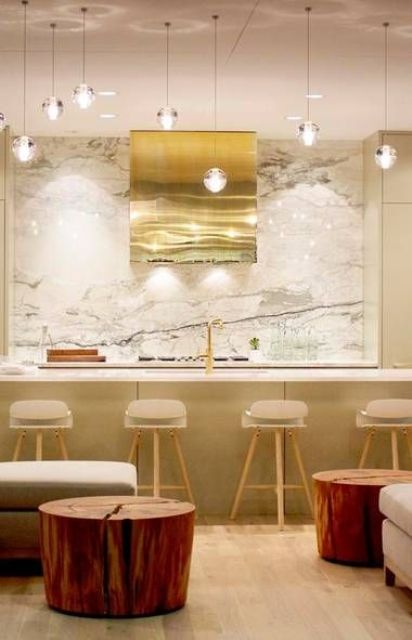 A Super Modern Glam Kitchen With Tan Furniture, A White Marble Wall And Countertops, Pendant Lamps, A Shiny Gold Hood And Gold Stools