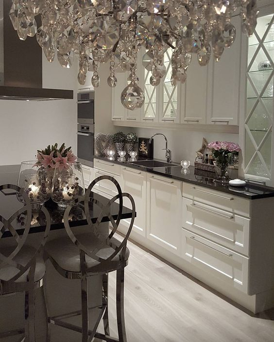 A Neutral Glam Kitchen With Black Countertops, Shiny Silver Stools, A Crystal Chandelier And Pink Florals