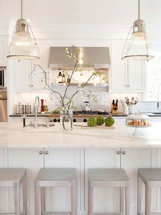 A Modern Neutral Kitchen With Touches Of Glam, With Neutral Furniture, White Marble Countertops, Pendant Lamps And Shiny Stools