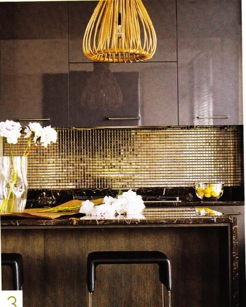 A Moody Glam Kitchen With Dark Cabinetry, A Shiny Gold Tile Backsplash, A Chandelier And Black Marble Countertops