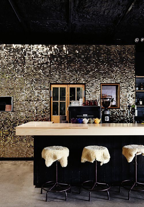 A Dark Glam Kitchen With Black Furniture, A Shiny Tile Backsplash, Neutral Stone Countertops And Faux Fur Stools