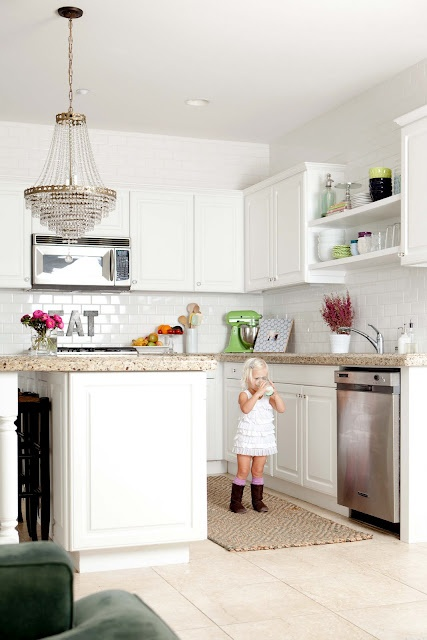 A Neutral Kitchen With White Cabinetry, Neutral Stone Countertops, A Chic Chandelier And A White Tile Backsplash