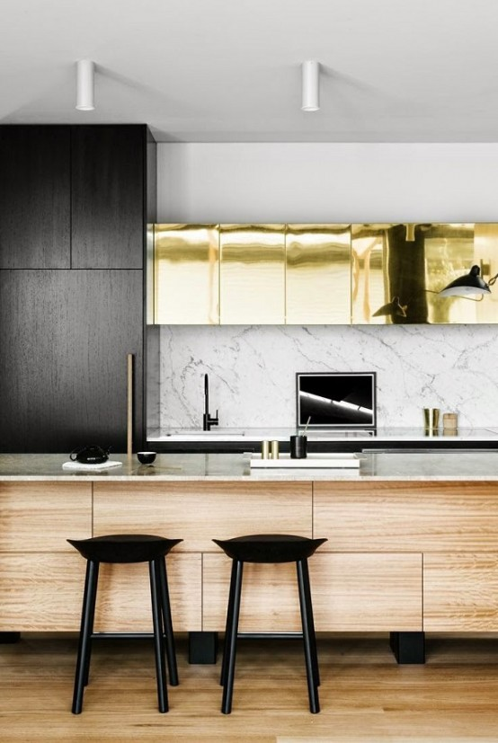 A Modern Glam Kitchen With Black And Shiny Gold Cabinets, A Wooden Kitchen Island With White Marble Countertops