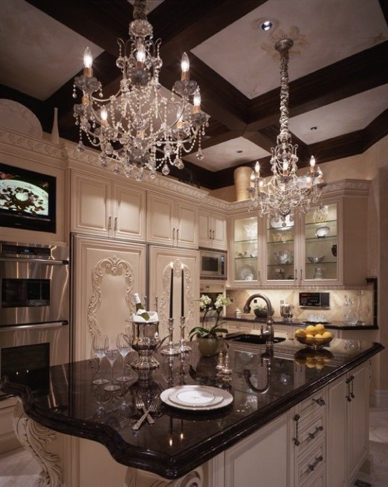 A Vintage Glam Kitchen With White Cabinetry, Dark Countertops, Molding On The Cabinets And Crystal Chandeliers