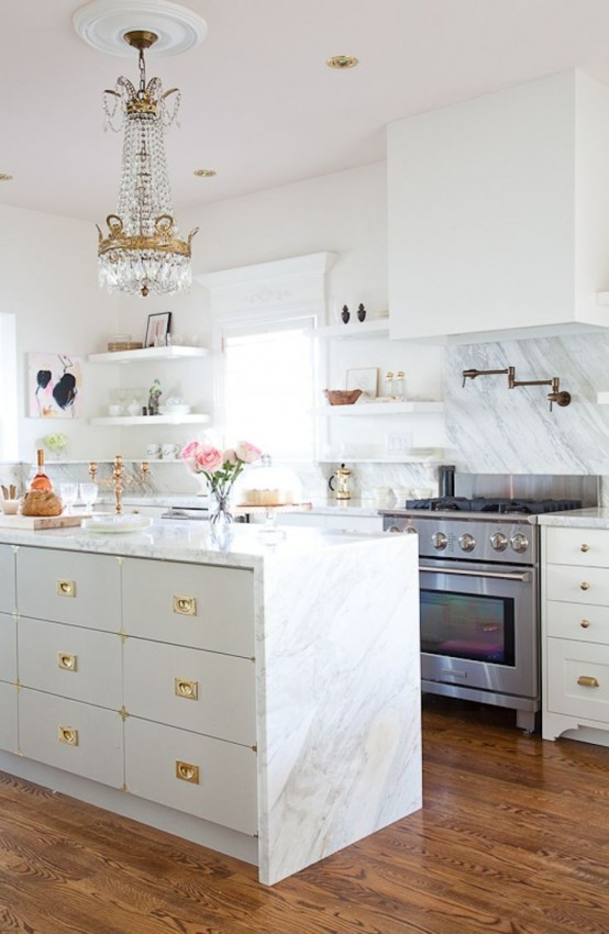 A White Glam Kitchen With Marble Countertops, Gold Handles And Knobs, A Vintage Crystal Chandelier Over The Space