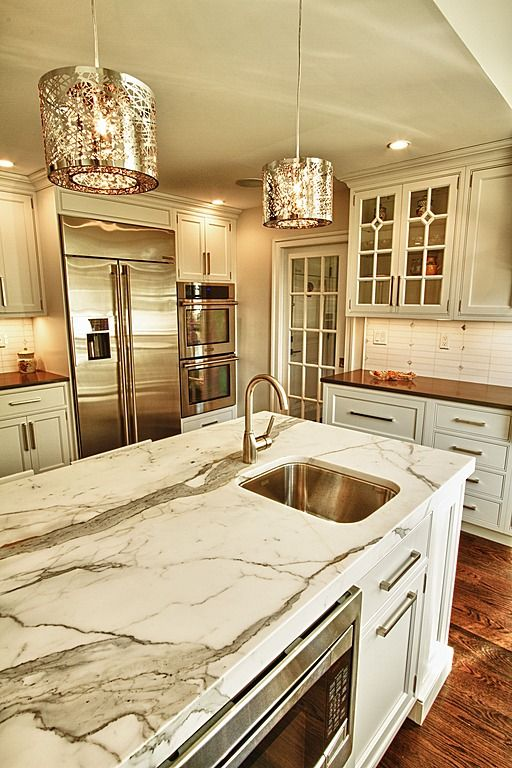 A Vintage Glam Kitchen With Neutral Cabinetry, Marble Countertops, Shiny Touches And Cool Metal Pendant Lamps