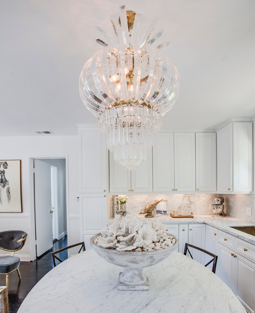 A Modern Glam White Kitchen With White Marble Countertops And A Backspalsh Plus A Gorgeous Glam Chandelier Over The Table