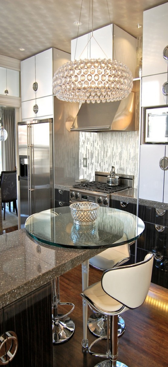 A Glam Kitchen With Dark Cabinetry, Shiny Silver Handles, A Large Crystal Chandelier And A Glass Countertop