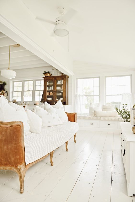 a French farmhouse sunroom done in white with an L-shaped white window seat, a refined sofa and potted greenery