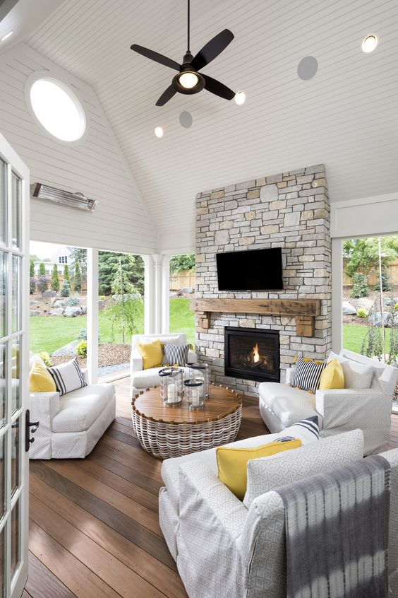 a modern farmhouse sunroom with white furniture, a stone clad fireplace, a rattan table and sunny yellow accents