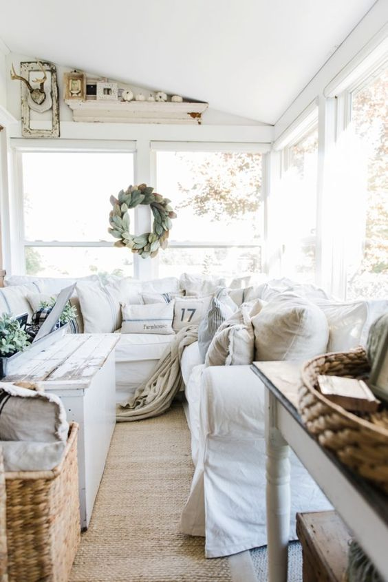a cozy neutral farmhouse sunroom with white furniture, baskets, a shabby chic table, a leaf wreath and white pumpkins