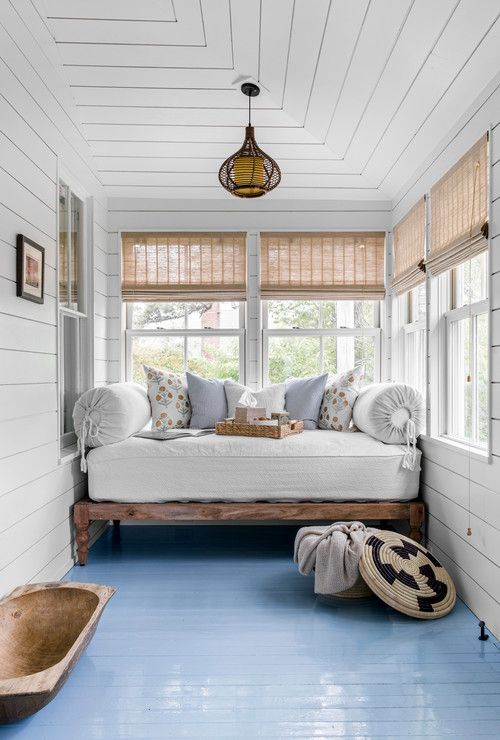 a chic country house sunroom with a daybed with a mattress and pillows, shades and a bread bowl is welcoming