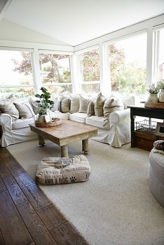 a simple farmhouse sunroom with an L-shaped white sofa, potted greenery, a rustic table and neutral textiles