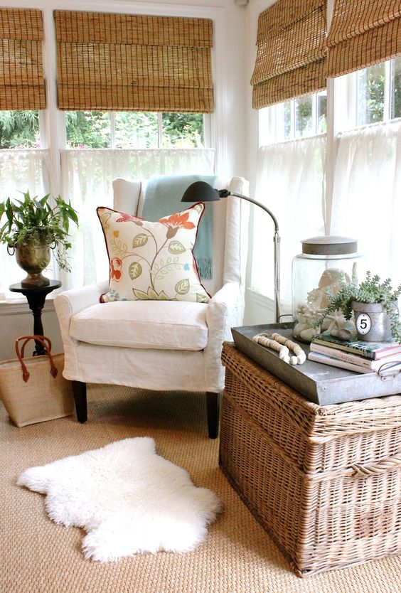 a rustic sunroom with shades, vintage and rattan furniture, layered rugs, potted greenery and lamps