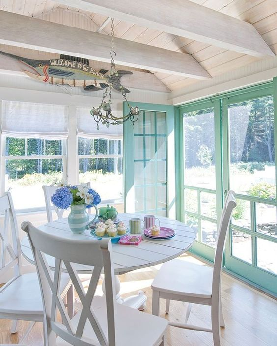 a white farmhouse sunroom with mint window frames, neutral textiles, a vintage chandelier and pastel touches