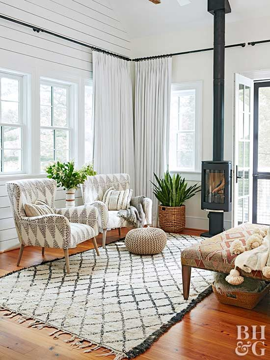 a stylish mid-century modern rustic sunroom with pritned textiles, chic furniture, potted greenery and a hearth