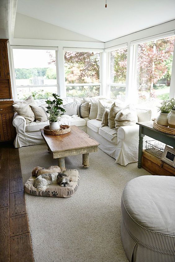 a welcoming farmhouse sunroom with a white L-shaped sofa, some vintage tables, baskets, neutral textiles and potted greenery