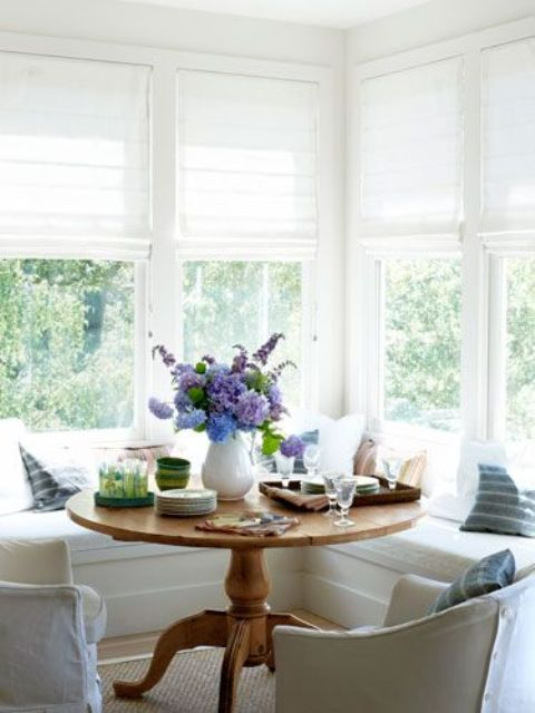 a neutral farmhouse sunroom corner with an L-shaped window seat and a rustic vintage table for having breakfasts here