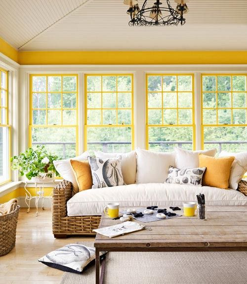 a bright farmhouse sunroom with sunny yellow window framing, wicker furniture, a vintage chandelier is very welcoming