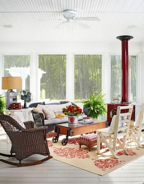 a rustic industrial sunroom with a red hearth, rattan and wooden furniture, a wooden table on casters and some potted greenery and blooms