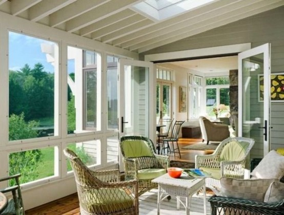 a bright farmhouse sunroom with rattan chairs of various colors, bright artworks and some pillows