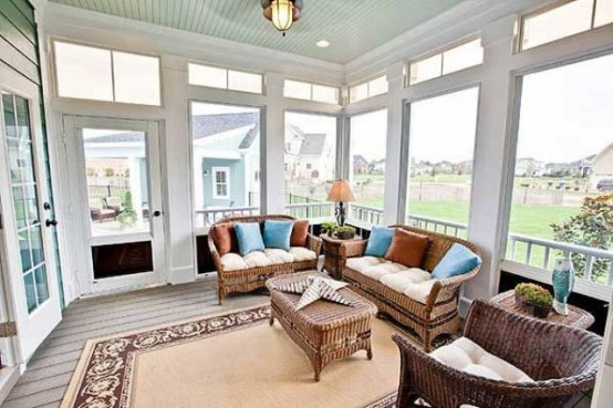 a farmhouse sunroom with rattan furniture, a rug, lamps and bright pillows that make the space more welcoming