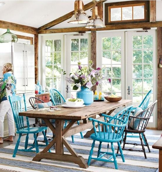 a bright farmhouse sunroom with stained wooden beams, a rustic wooden table, bright blue chairs and vintage pendant lamps