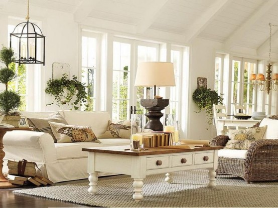 a neutral farmhouse sunroom in vintage style, with rattan, wooden and upholstered furniture, lots of potted greenery and hanging lamps