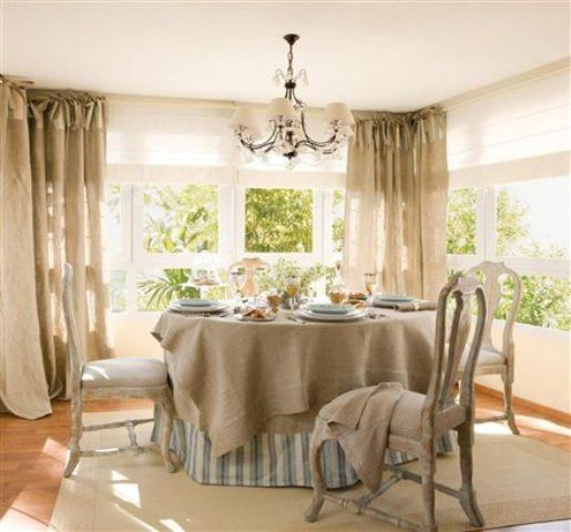 a neutral farmhouse sunroom with a dining zone with neutral vintage furniture, burlap curtains and linens and a vintage chandelier