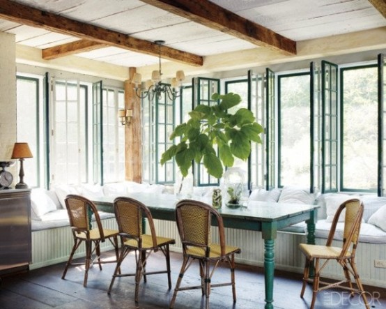 a farmhouse sunroom with a dining zone  with a long L-shaped window seat, a blue table and rattan chair plus wooden beams