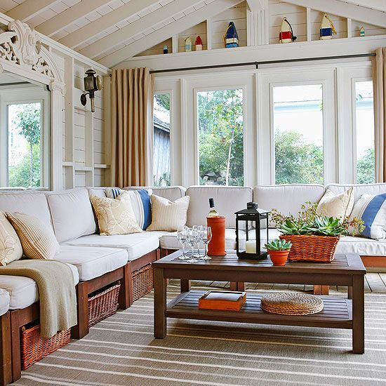 a cozy farmhouse sunroom with wicker furniture, neutral upholstery, orange and blue accessories and lots of large succulents