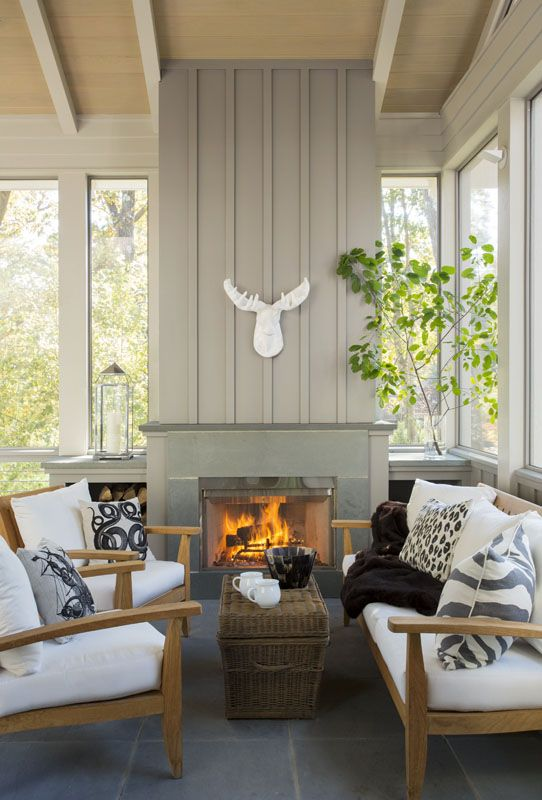 a farmhouse sunroom nook with a fireplace, wooden furniture with white upholstery, greenery and a skull
