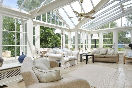 a large neutral farmhouse sunroom with neutral furniture, pendant lamps and some tables is a cool salon for guests
