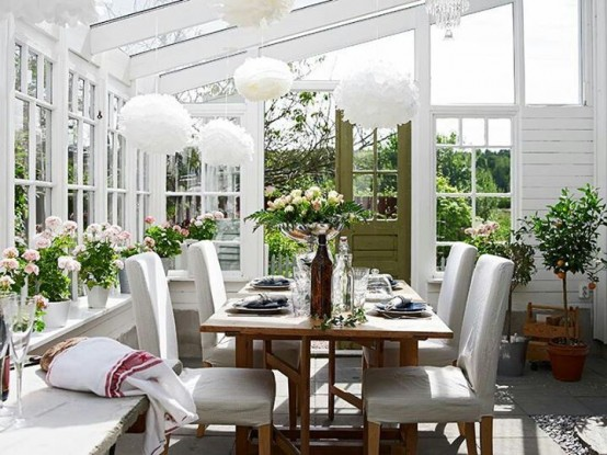 a white farmhouse sunroom with white furniture, a wooden table, fluffy pendant lamps and potted greenery and blooms is very cozy