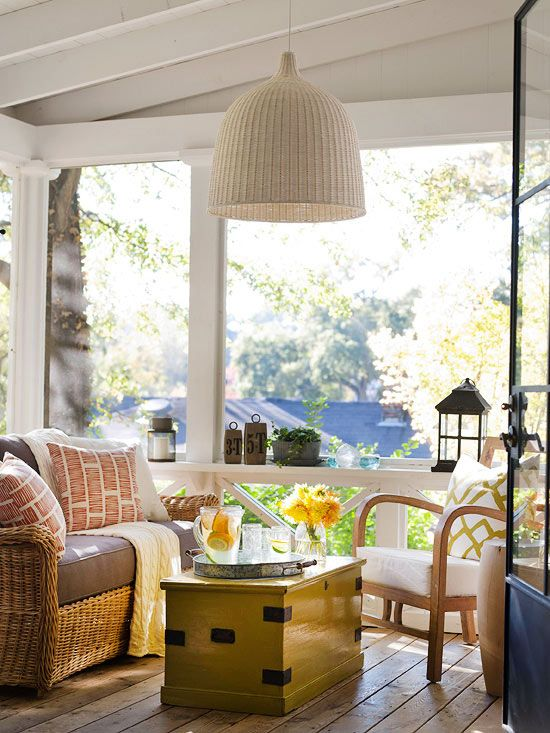 a neutral farmhouse sunroom with wooden and rattan furniture, bright printed pillows and candle lanterns and blooms is very inviting