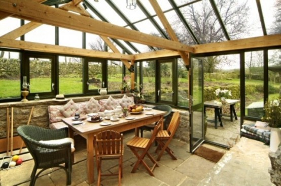 a rustic sunroom in a former glasshouse, with wooden and rattan furniture and a cozy pink loveseat is great for dining here
