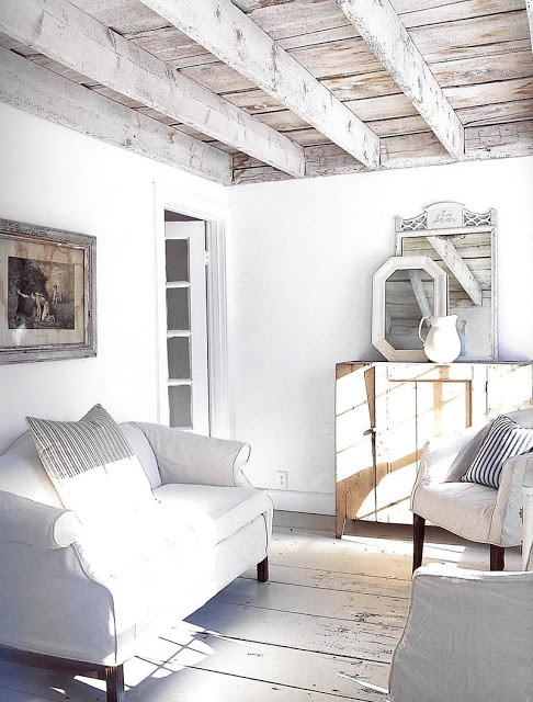 a whitewashed rustic sunroom with a whitewashed ceiling, vintage refined furniture and vintage mirrors