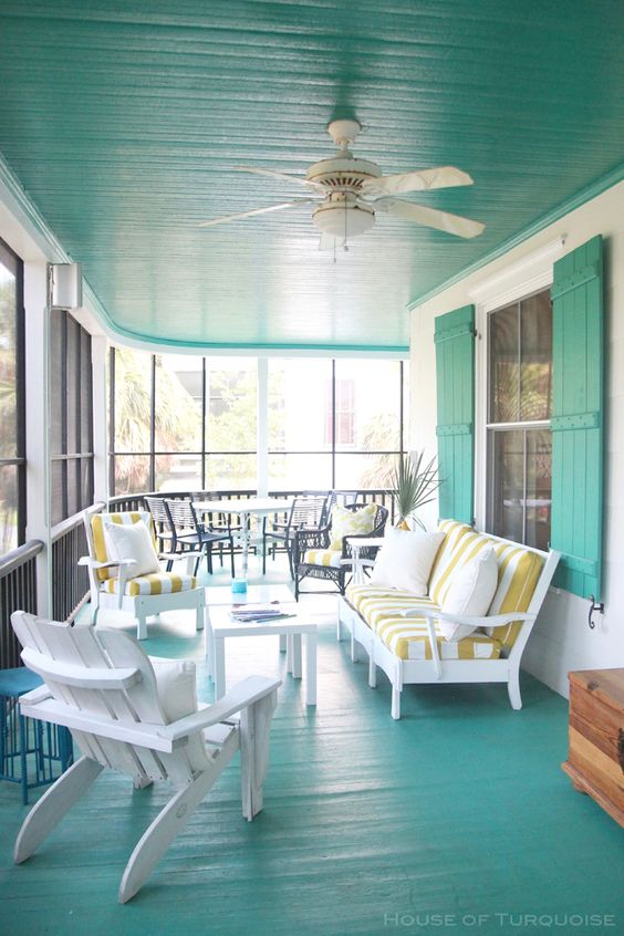a bright mint blue sunroom with white wooden furniture, striped upholstery and a cozy dining space