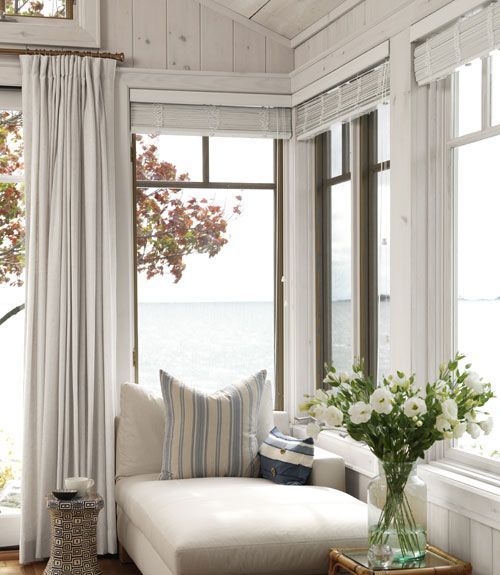a coastal sunroom with a modern neutral daybed, striped pillows and neutral textiles plus gorgeous sea views