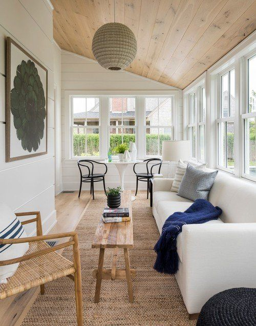 a coastal sunroom with mid-century modern furniture, a navy blanket, a cool artwork and a woven pendant lamp