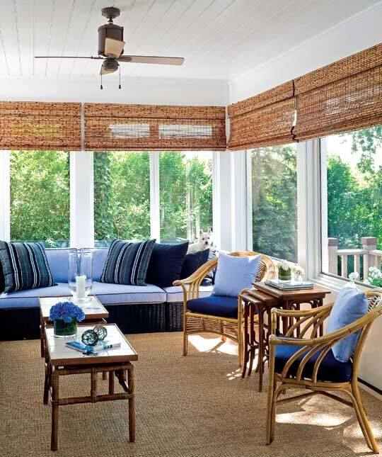 a bright beach sunroom with a rattan furniture, bright blue and navy upholstery and bamboo tables and shades