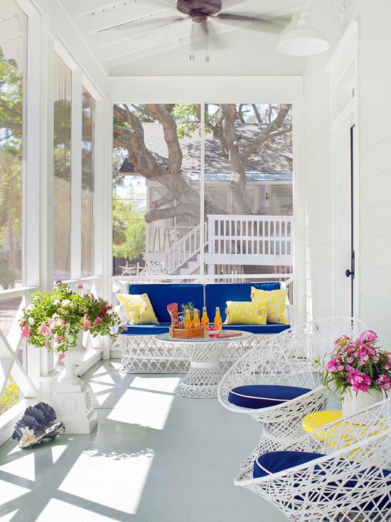 a bright modern beachy sunroom with white metal furniture with super bold upholstery, some potted blooms and seashells