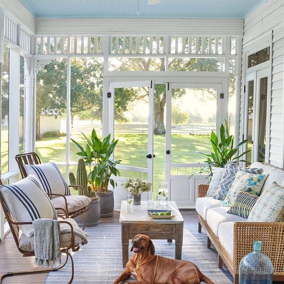 a beachy sunroom with rattan furniture, printed textiles, a wooden table and some potted plants