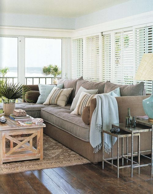 a beach sunroom with chocolate brown and light blue furniture, wooden and metal tables and potted greenery