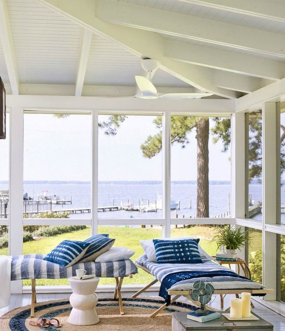 a simple beach sunroom with wooden daybeds, printed textiles, a wooden chest and candles plus cool views