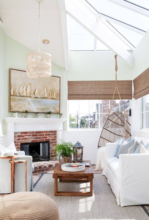 an elegant coastal sunroom with white and light blue furniture, woven shades, a brick fireplace, a woven lamp and a coastal artwork