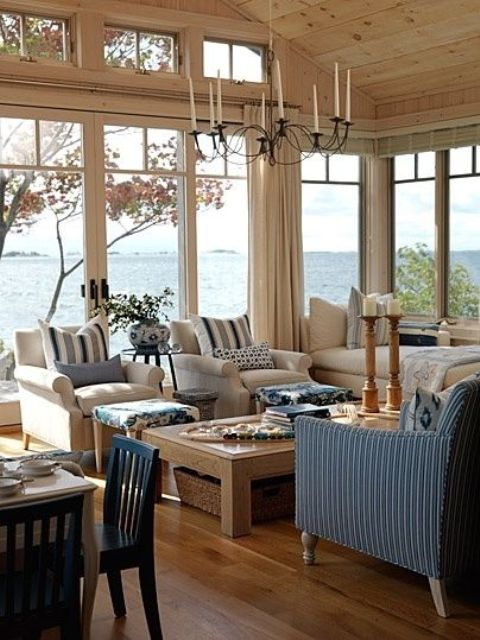 a coastal sunroom in rustic style with neutral and blue furniture, a wooden table with baskets and a vintage chandelier