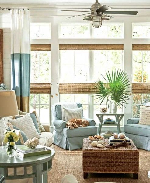a coastal sunroom with neutral and light blue furniture, color block curtains, woven shades and a wicker table plus greenery