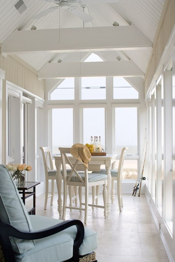 a vintage-inspired coastal sunroom with white and black vintage furniture, ligth blue upholstery, chic sea views
