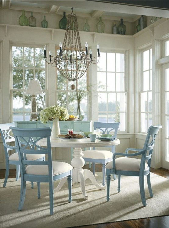 a vintage rustic coastal sunroom with a dining zone, blue furniture, a vintage chandelier and some bottles for decor